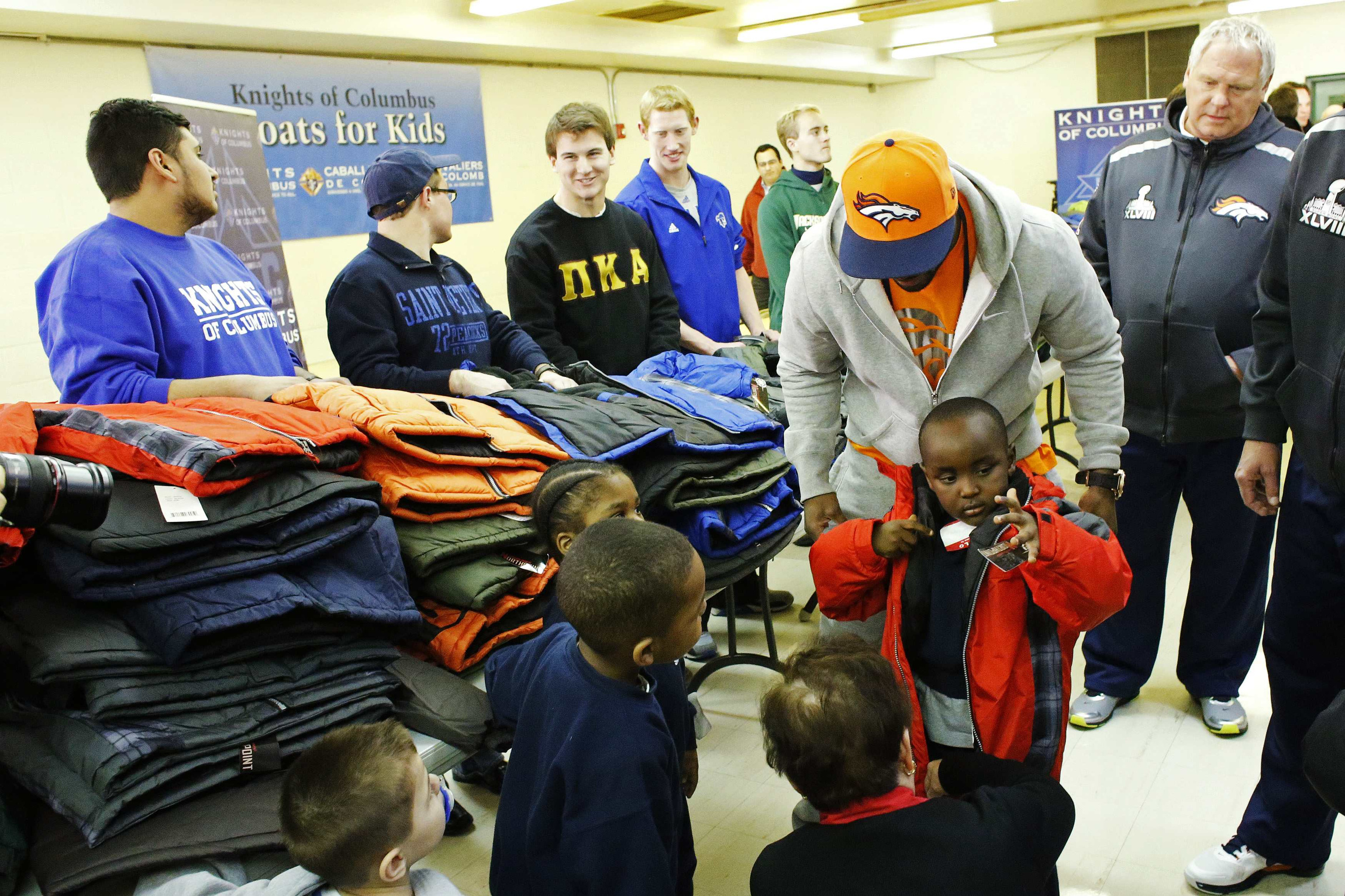 "Denver Broncos running back Knowshon Moreno helps a boy try on a jacket during a charitable event with the Knights of Columbus called ""Coats for Kids"" in Jersey City, N.J., Jan. 28. The Broncos were in New Jersey to face the Seattle Seahawks in Super Bowl XLVIII Feb. 2 at MetLife Stadium in East Rutherford, N.J. (CNS photo/Eduardo Munoz, Reuters) (Jan. 29, 2014)"
