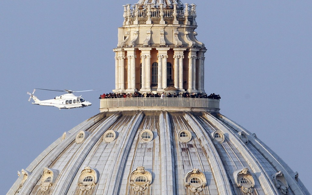 Helicopter carrying Pope Benedict XVI flies past St. Peter's Basilica as it leaves Vatican