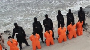 Still image from video shows men purported to be Egyptian Christians kneeling in front of armed men along beach said to be near Tripoli