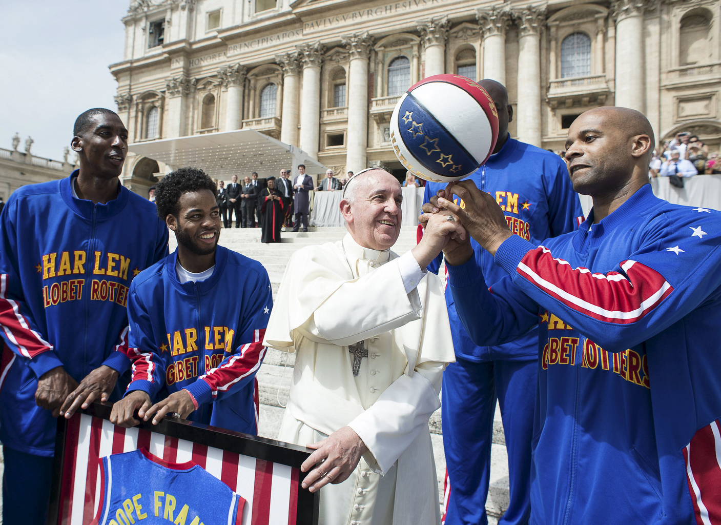 Pope Francis smiles as he plays with a basketball next to members of the Harlem Globetrotters basketball at Vatican