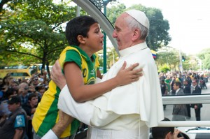 Pope Francis embraces boy as he arrives to hear confessions during World Youth Day in Rio de Janeiro