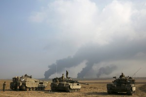 Israeli soldiers stand atop tanks outside northern Gaza Strip