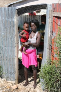 Woman stands with son outside makeshift home in Canaan, Haiti